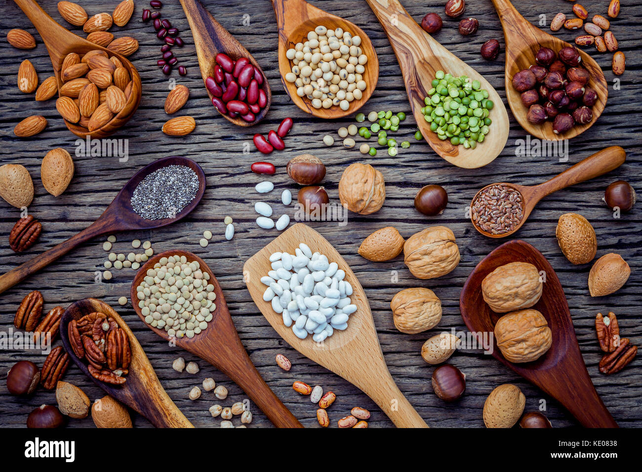 Various legumes and different kinds of nutshells in spoons. Walnuts kernels ,hazelnuts, almond ,brown pinto ,soy - Stock Image