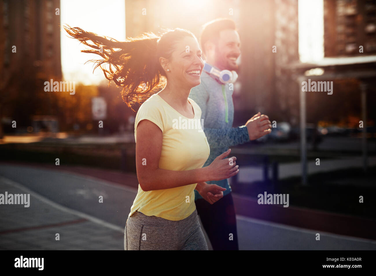 Young attractive couple running outside on sunny day - Stock Image
