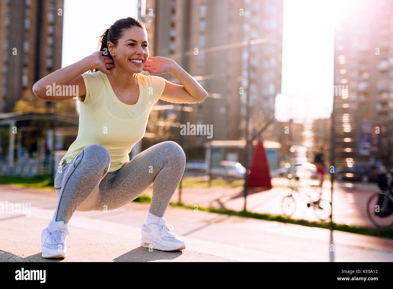 Young woman doing squats in urban area - Stock Image