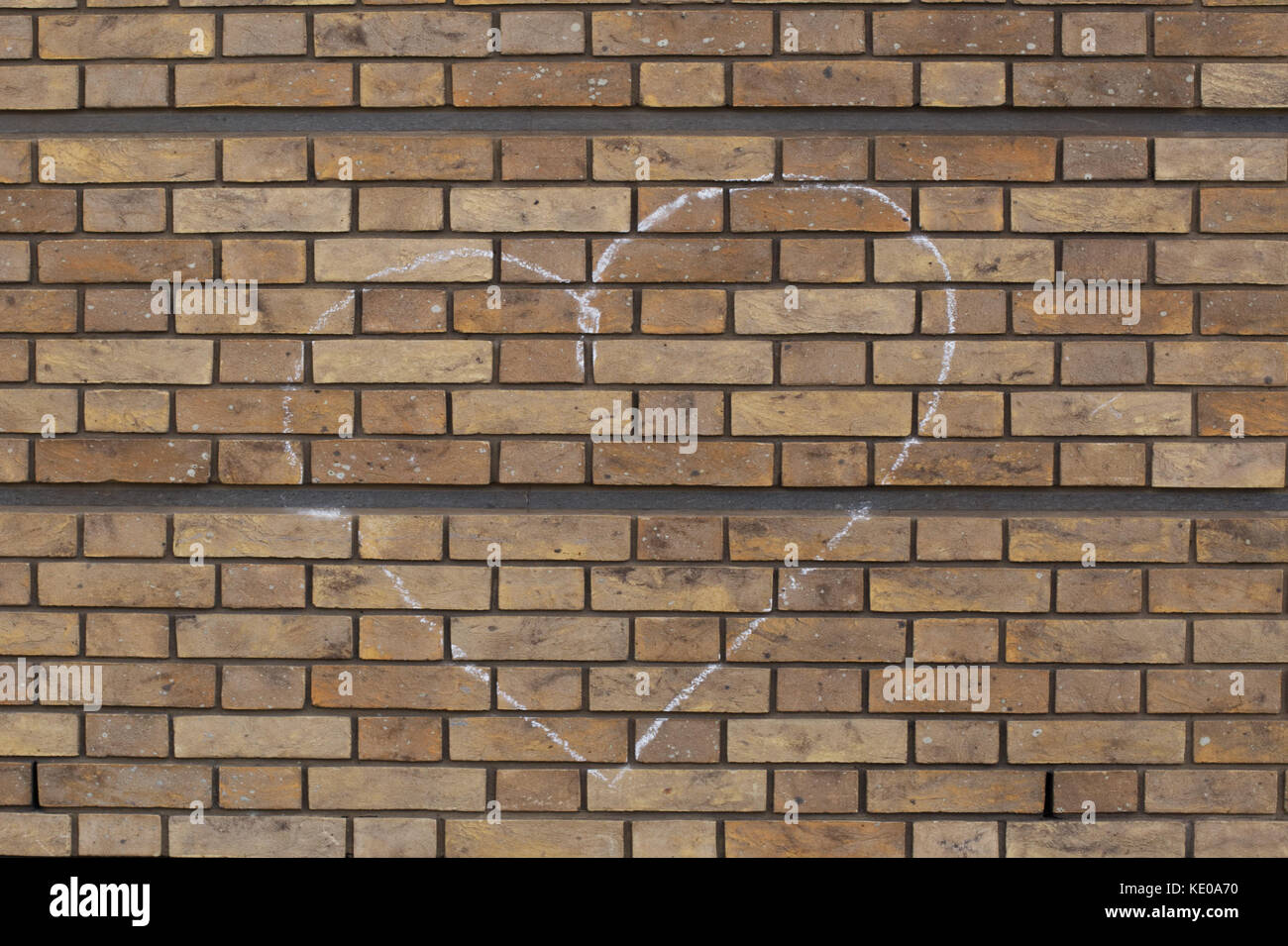 heart drawn in chalk on a brick wall - Stock Image