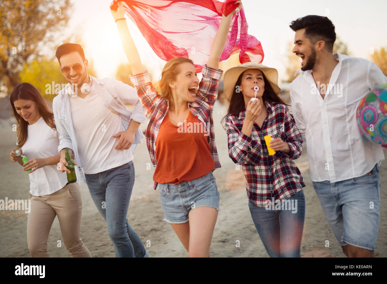 Group of happy young friends having great time on beach - Stock Image