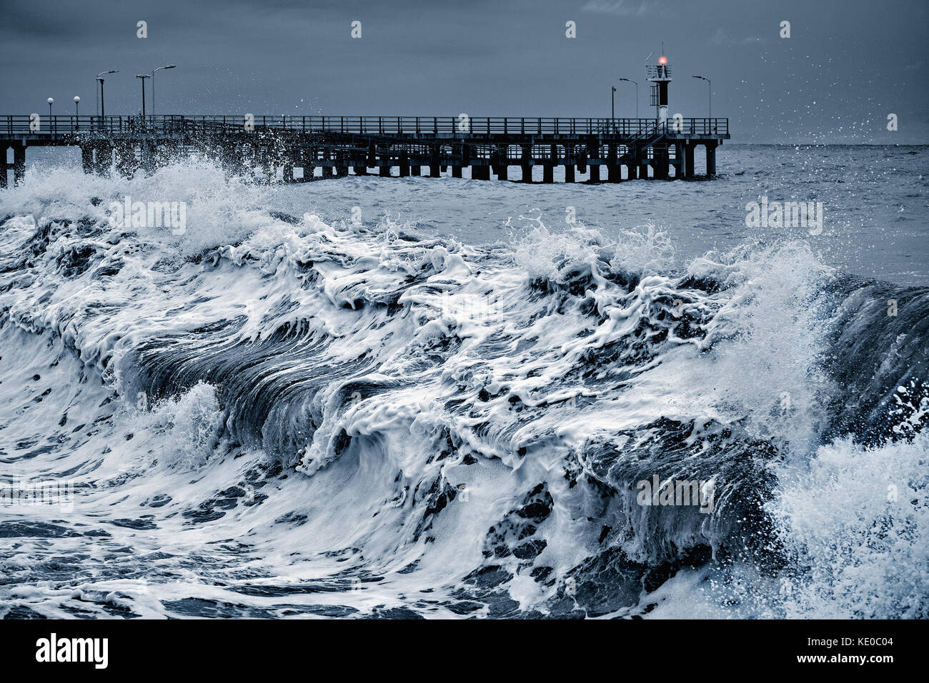 View of the pier at stormy evening time. - Stock Image