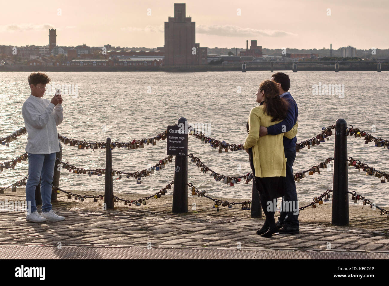 Pier Head, Liverpool, UK. A couple have their photograph taken beside the River Mersey. The railings are covered - Stock Image