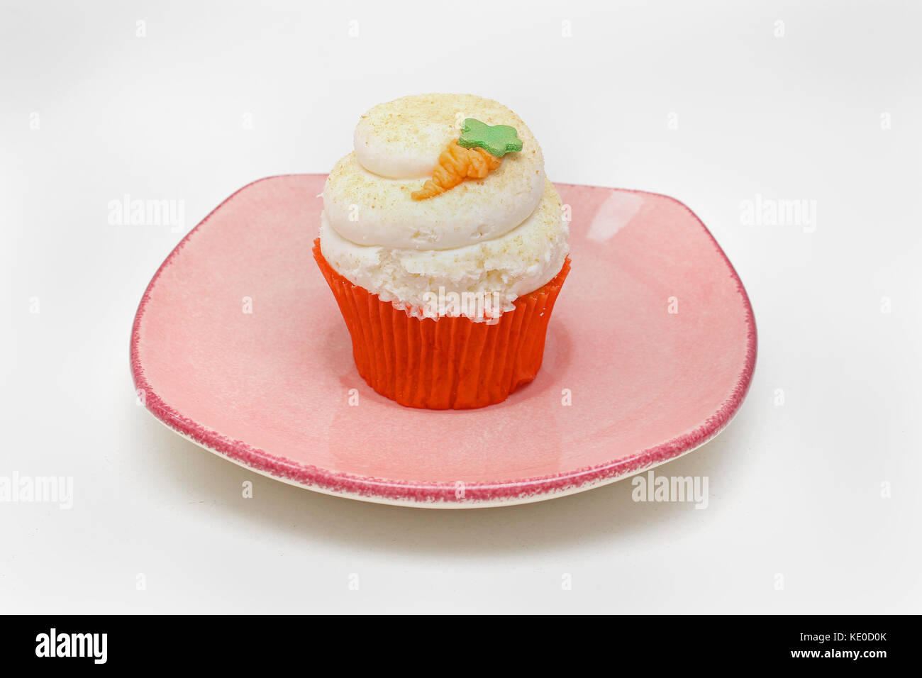 Cupcake dessert on pink plate with carrot decoration - Stock Image