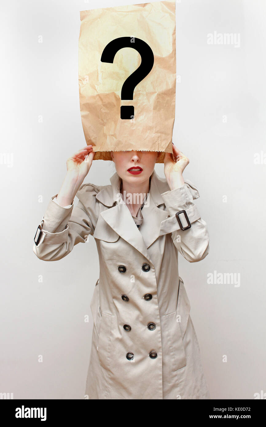 Young woman in trench coat hides her identity with face covered under paper bag with question mark - Stock Image