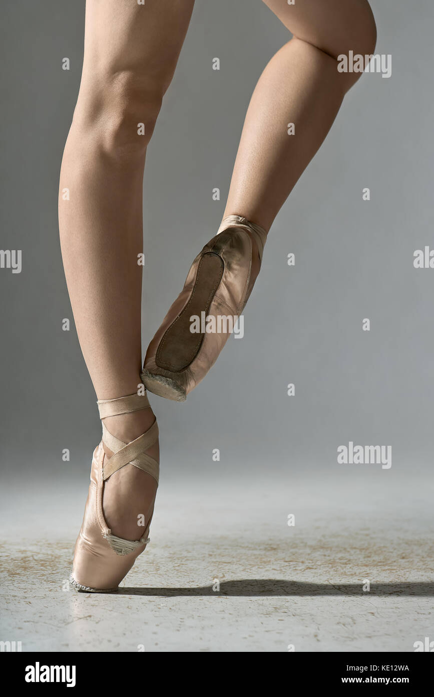Ballet dancer is posing in the studio on the gray background. She stands on the right toe and holds left foot on - Stock Image