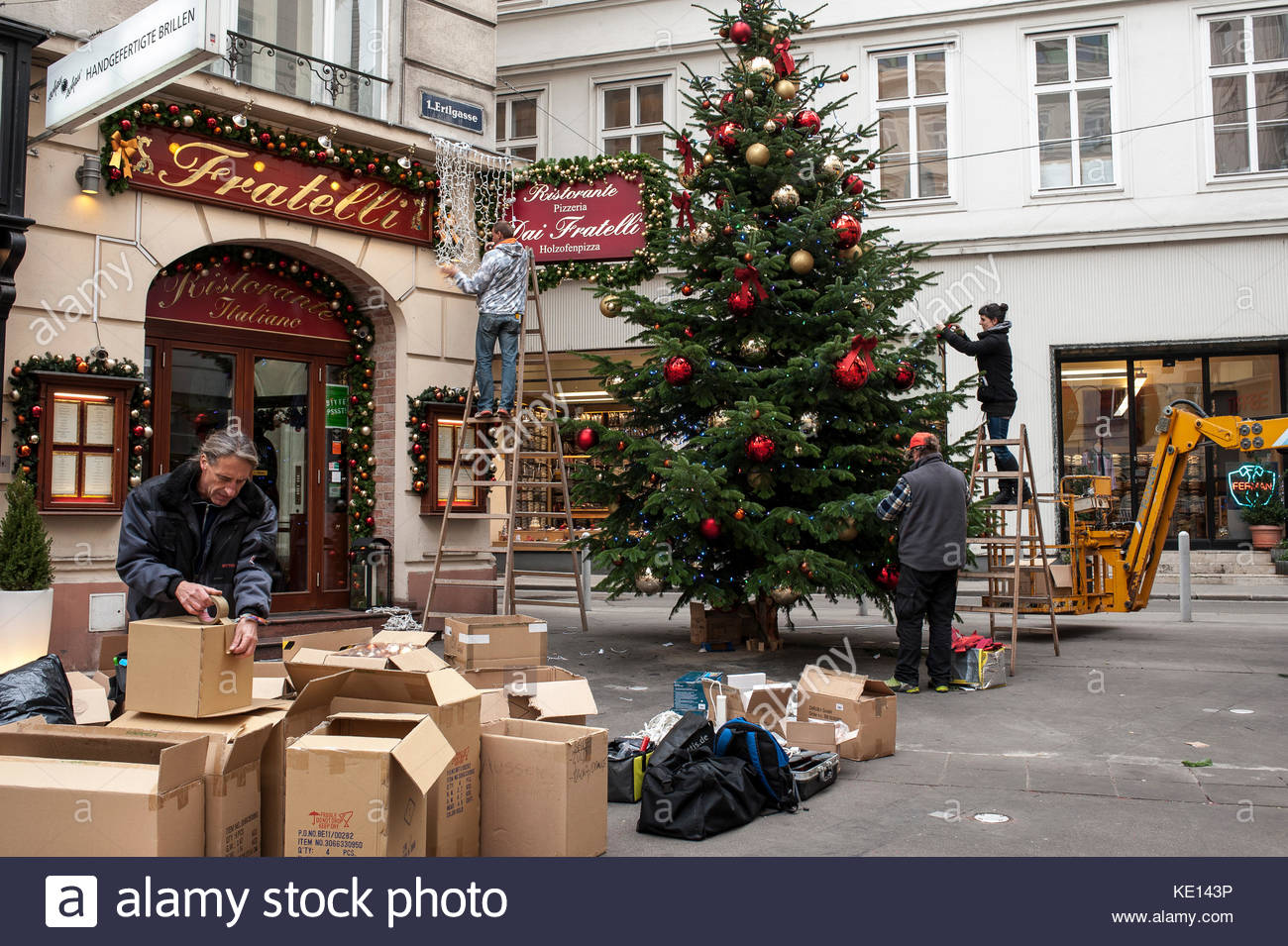 A Group Of Workers Erect A Christmas Tree And Decorate The Shops At  Ertlgasse In The First District Of Vienna, Austria.