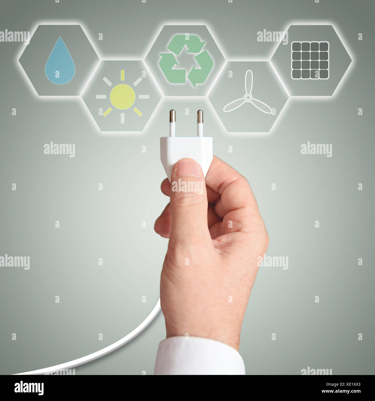 Business man holding a plug. Renewable energy concept. - Stock Image
