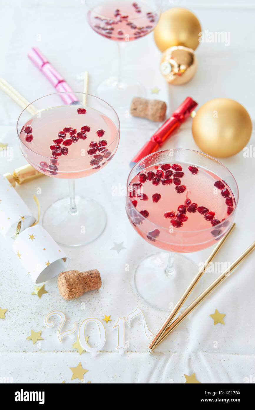 Pink bubbly cocktail and festive christmas decorations - Stock Image