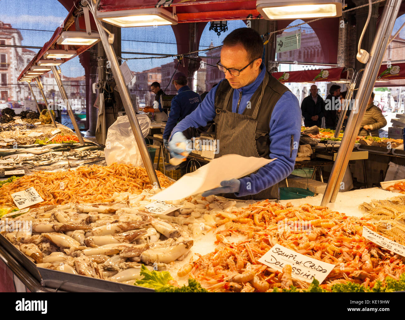 VENICE ITALY VENICE fishmonger selling fresh fish and seafood from the Market stalls selling fresh fish in the Rialto - Stock Image