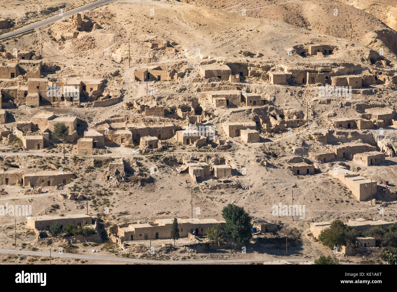 Zoomed view on Kings Highway of desert valley with mud brick houses in a village, Jordan, Middle East - Stock Image