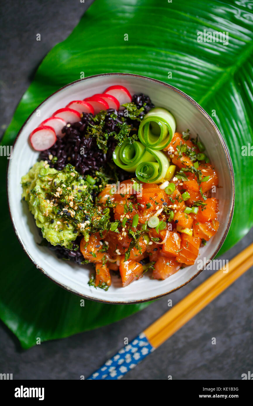 Salmon ahi poke with black forbidden rice, pickled cucumber, avocado and radishes - Stock Image