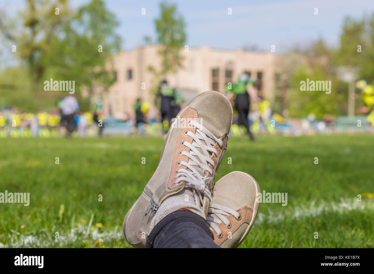 Close up of female watching football game: snickers shoes on background of American football match - Stock Image