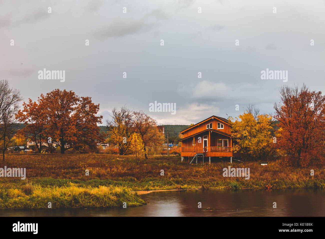 riverside cottages around autumn trees on lake Stock Photo