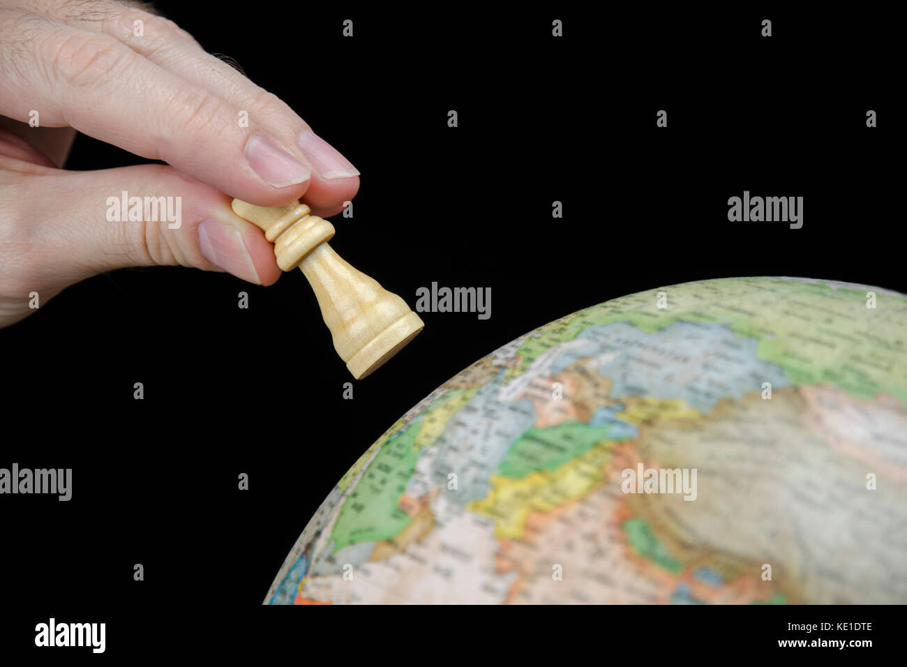 Close-up view of a hand holding a chess piece over a globe isolated on a black background - Stock Image