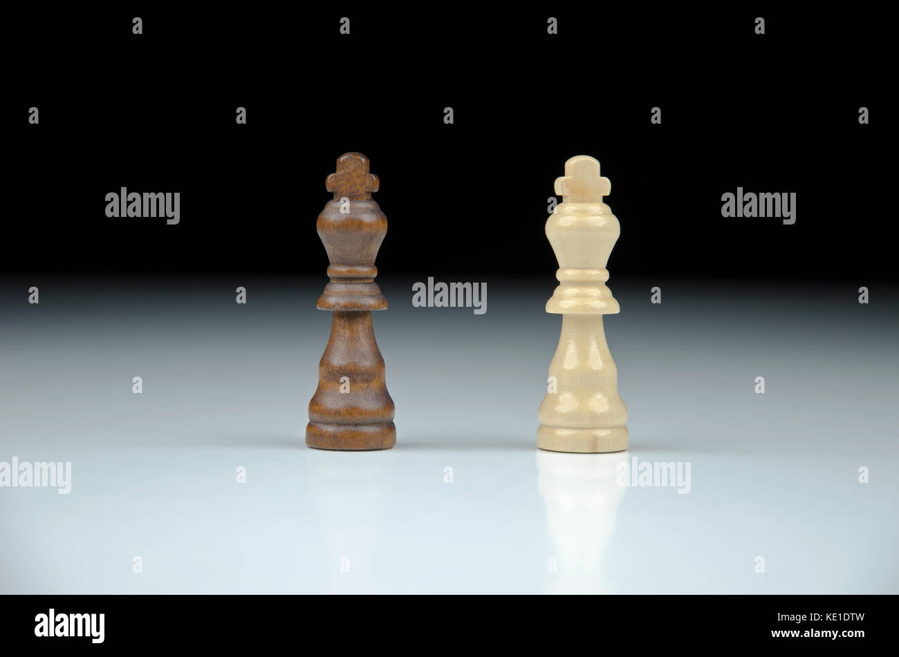 Close-up view of two chess king on blurred black and white background with reflection - Stock Image