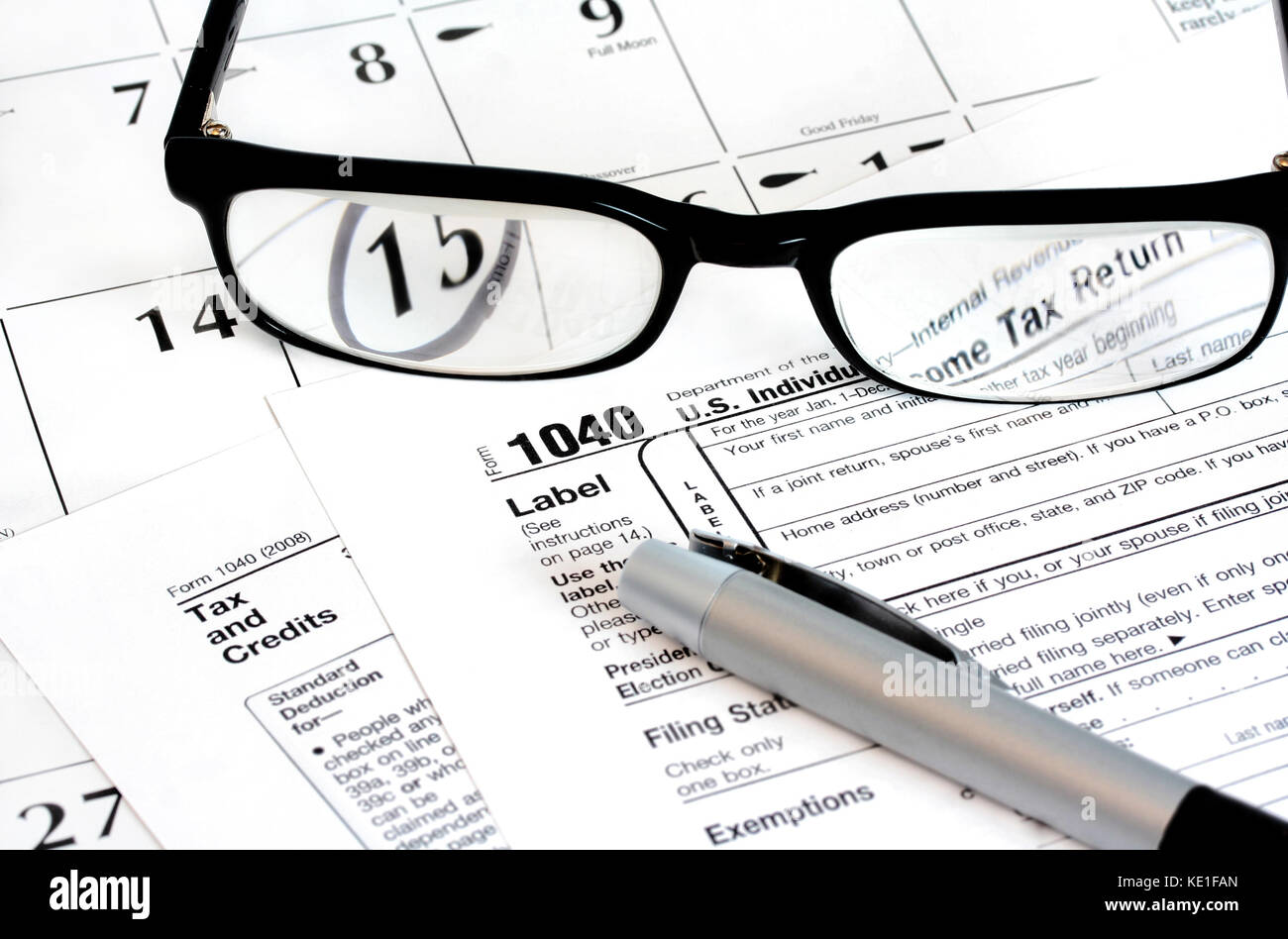 Federal income tax 1040 form on a calendar with the 15th noted on it with a pen and glasses on top of it. Stock Photo