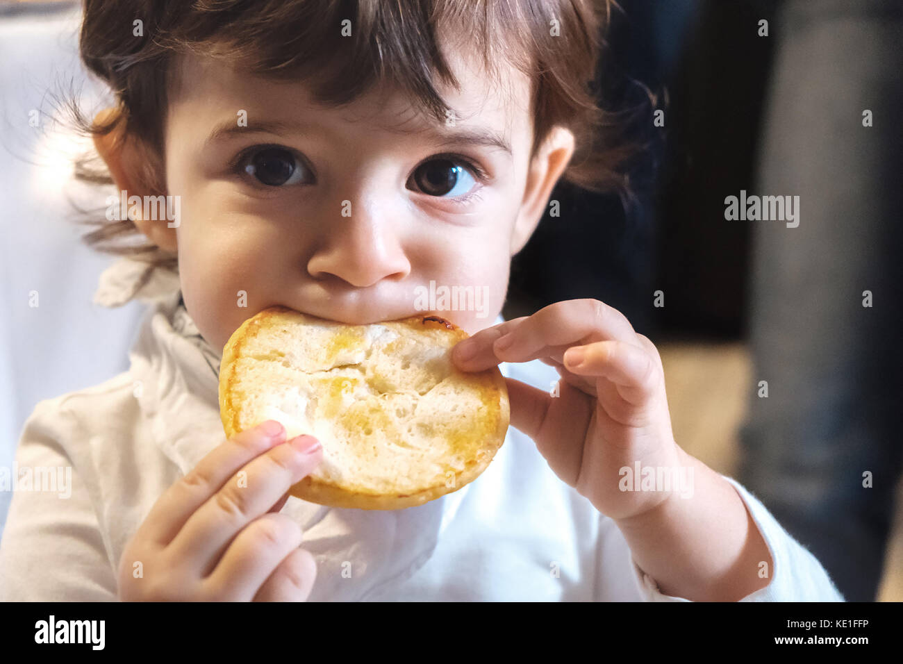 baby child eat carbohydrates -  newborn eating face closeup portrait - unhealthy diet for kids Stock Photo