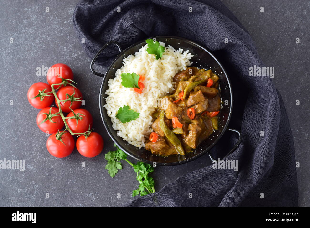 Attractive Pork In Spicy Curry Sauce With Eggplant And Green Beans, Served With Cooked  Rice In A Black Metal Bowl On A Grey Abstract Background. Home Cooking