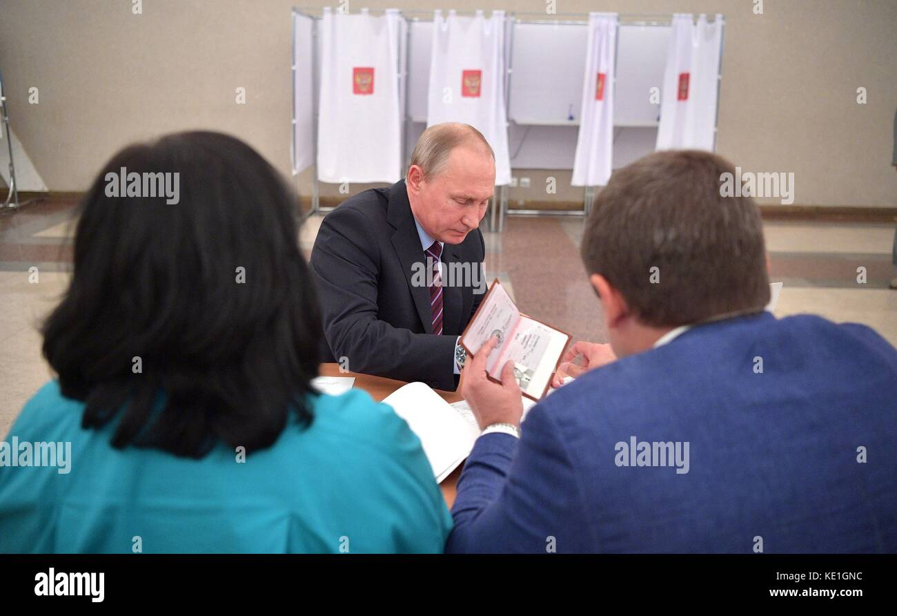 Russian President Vladimir Putin shows his identification papers as he arrives to vote in municipal elections at - Stock Image