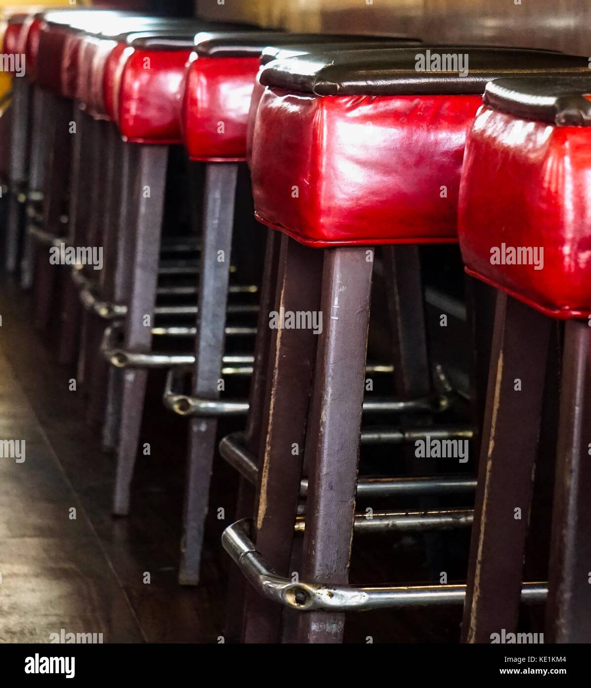 empty red leather barstools lined up in a row at counter - Stock Image