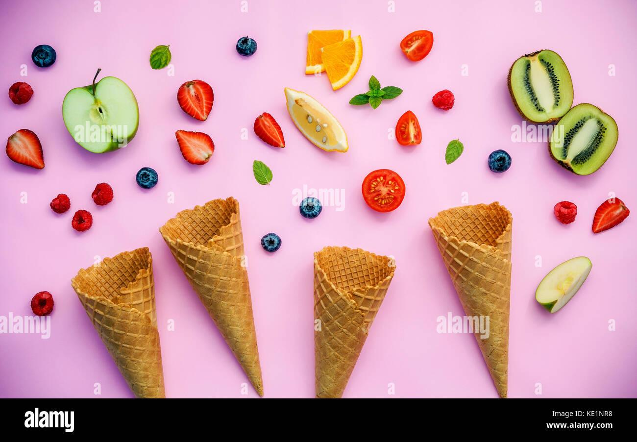 Cones and colorful various fruits raspberry ,blueberry ,strawberry ,orange slice , halved kiwi ,apple,tomato and - Stock Image