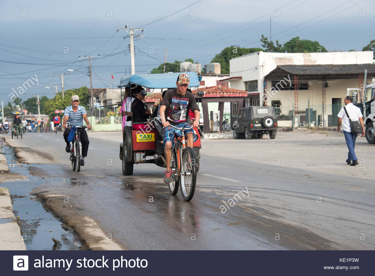 Urban transportation and unhygienic street. 'Motoneta' used for commuting and bicycle passing by the road - Stock Image