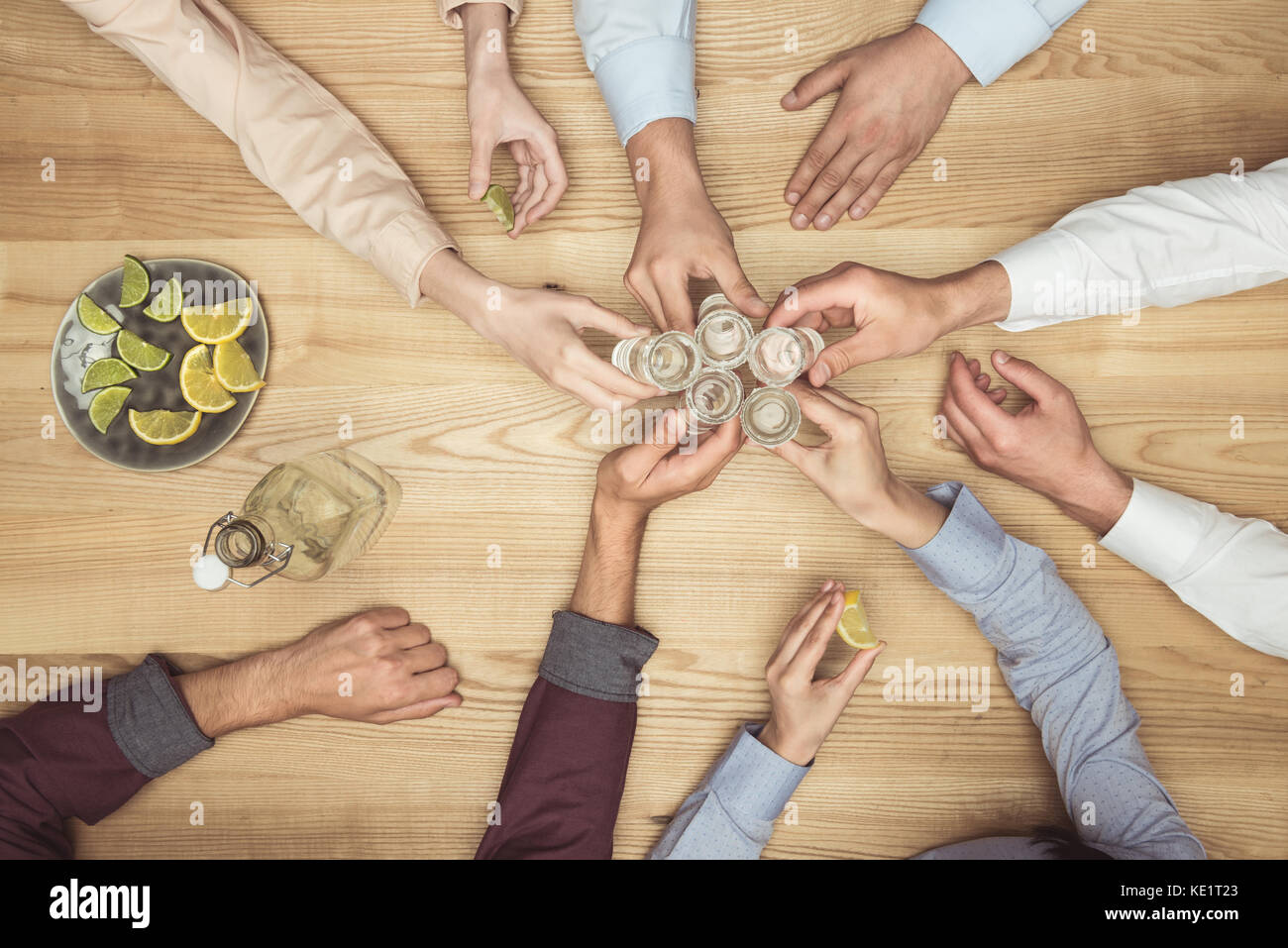 top view of friends hands with tequila shots on wooden tabletop  - Stock Image