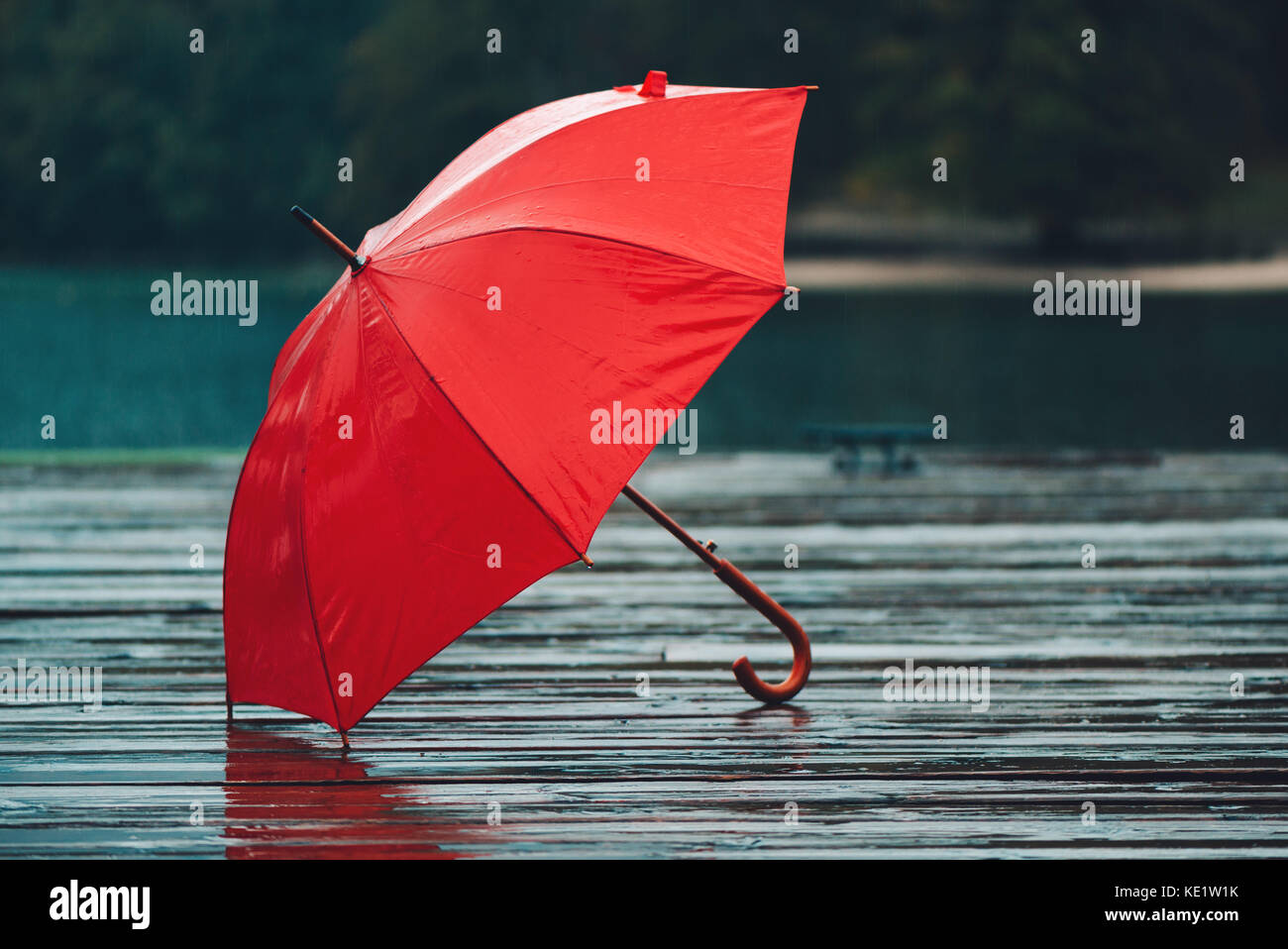 Red umbrella on rain, personal accessory forgotten on old wooden pier - Stock Image