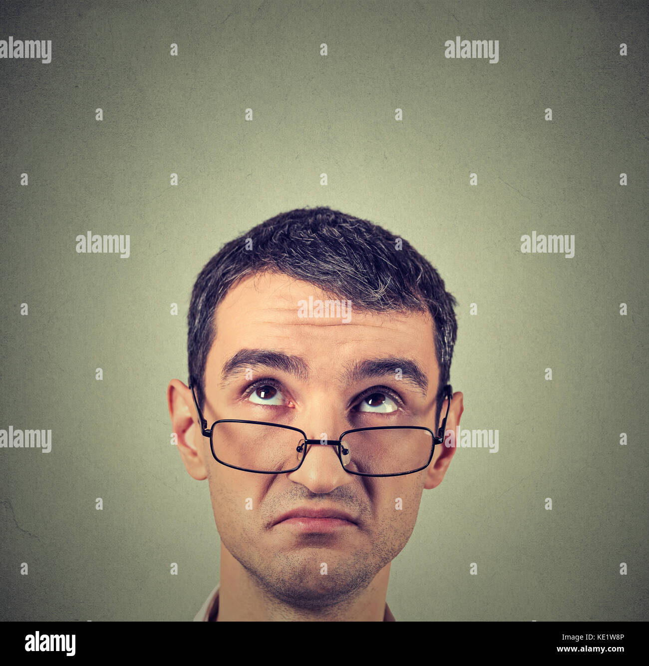 Closeup funny confused skeptical man in glasses thinking planning looking up above head isolated gray wall background Stock Photo