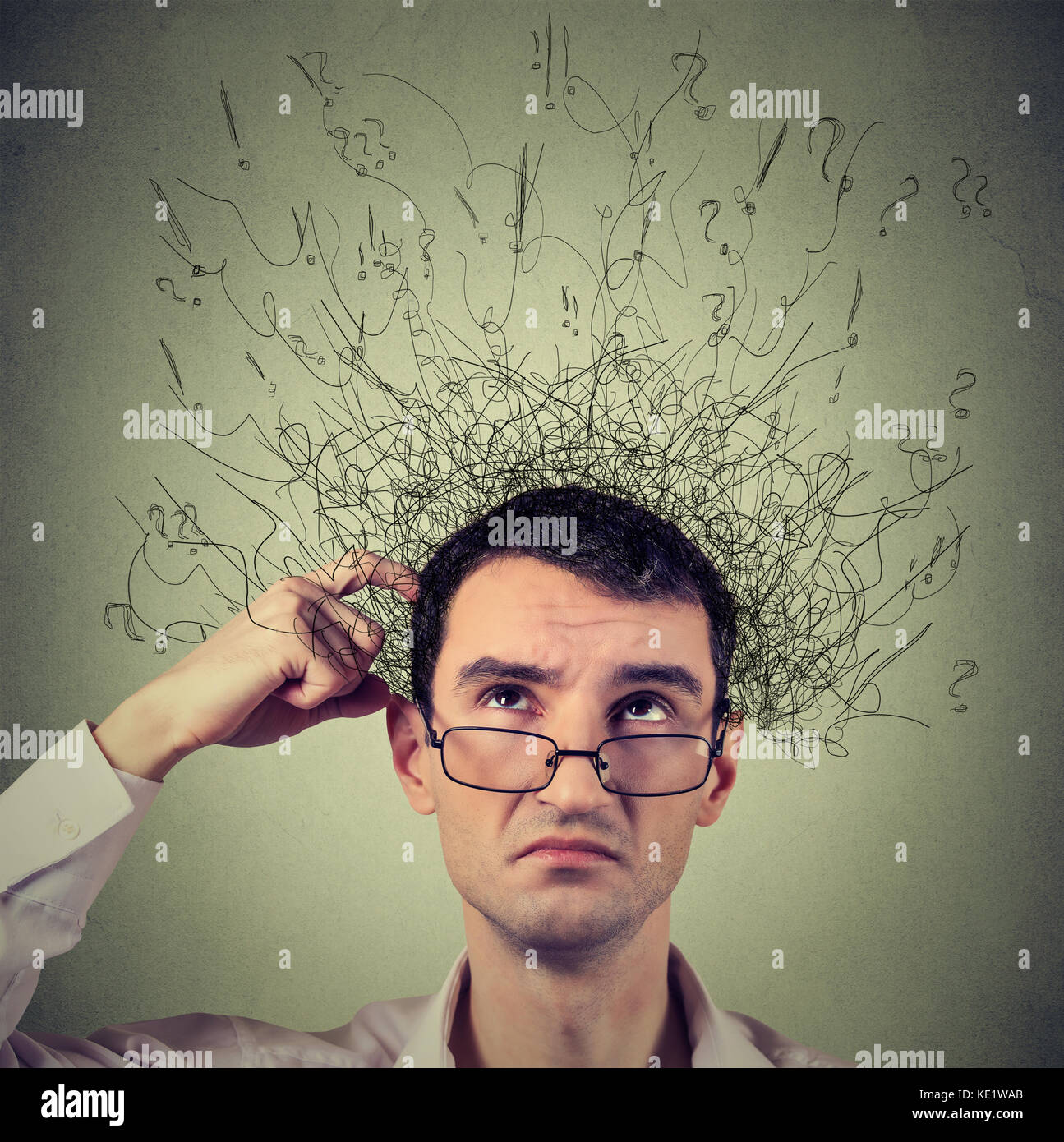 Closeup portrait young man scratching head, thinking daydreaming with brain melting into many lines question marks - Stock Image