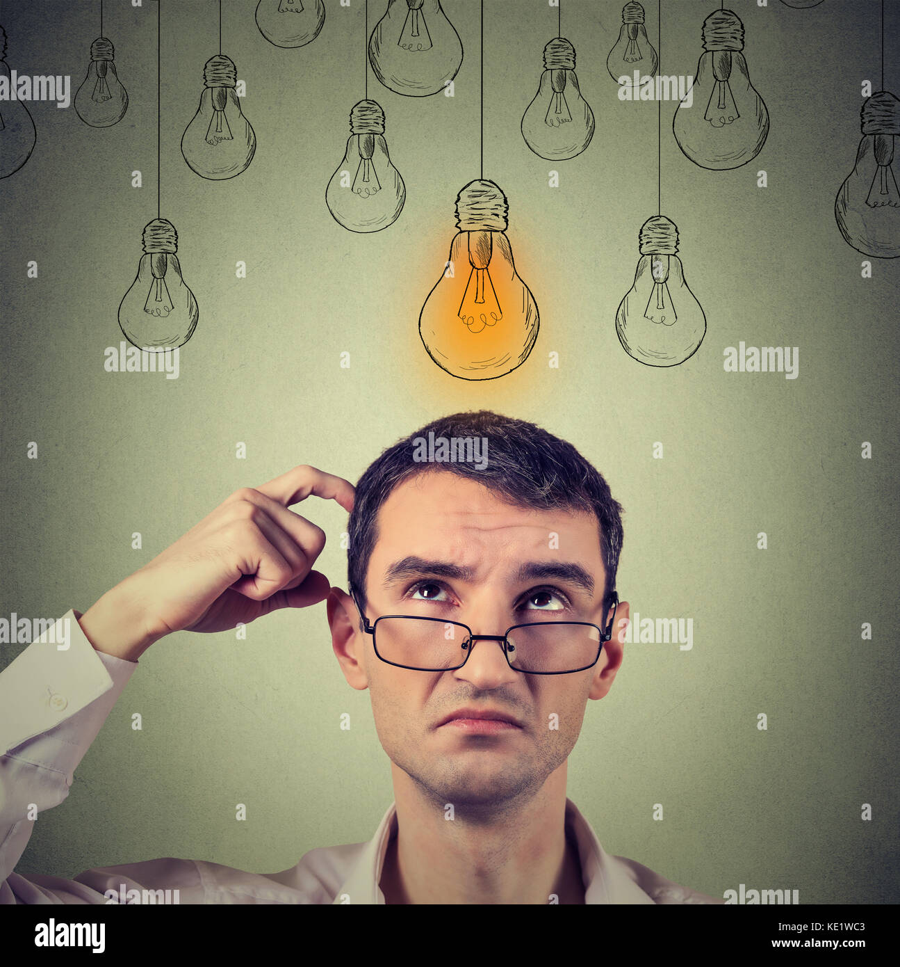 Portrait thinking man in glasses looking up with light idea bulb above head isolated on gray wall background Stock Photo