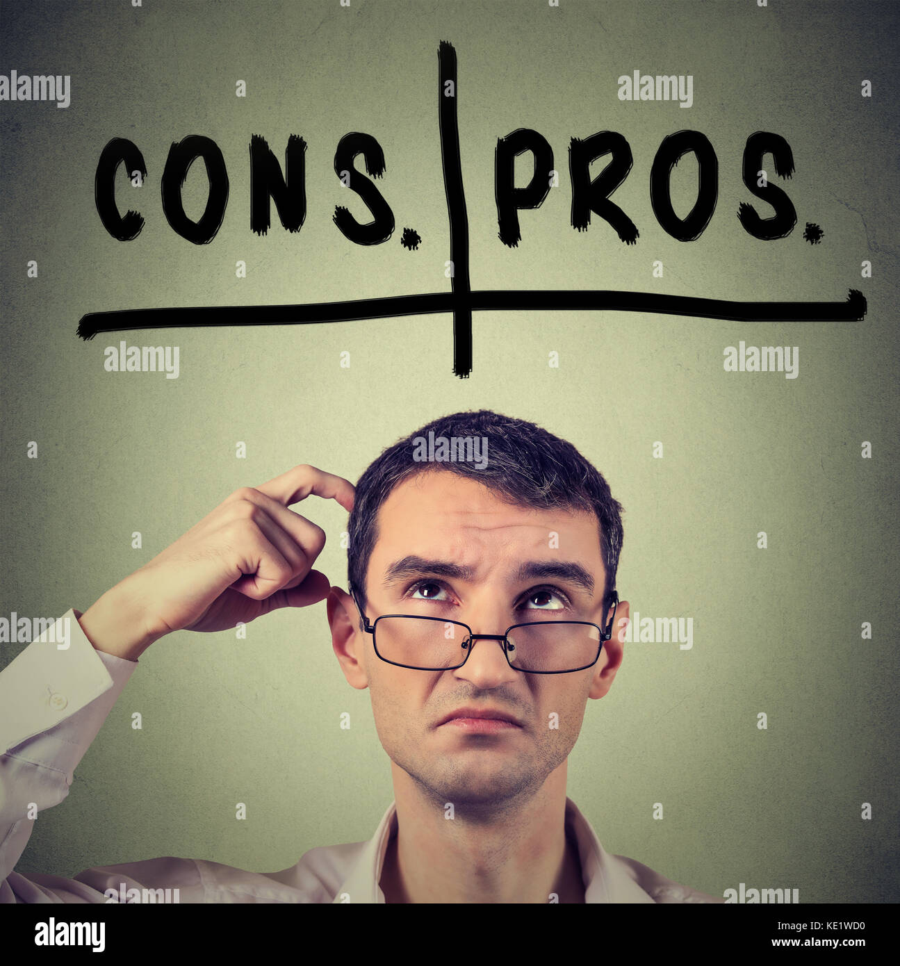 pros and cons, for and against argument concept. Young business man with glasses looking up deciding isolated on - Stock Image