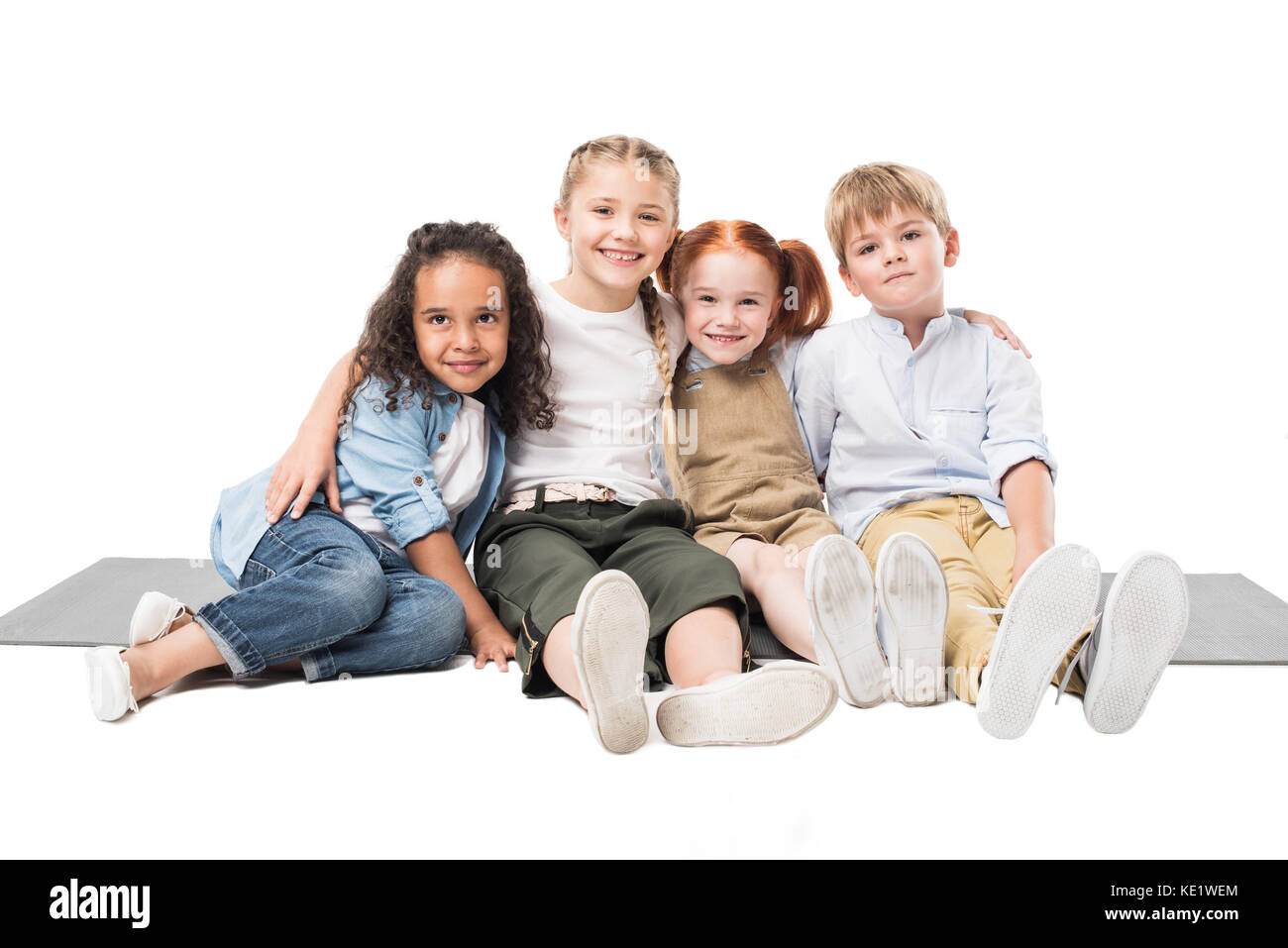 happy multiethnic children sitting together isolated on white - Stock Image