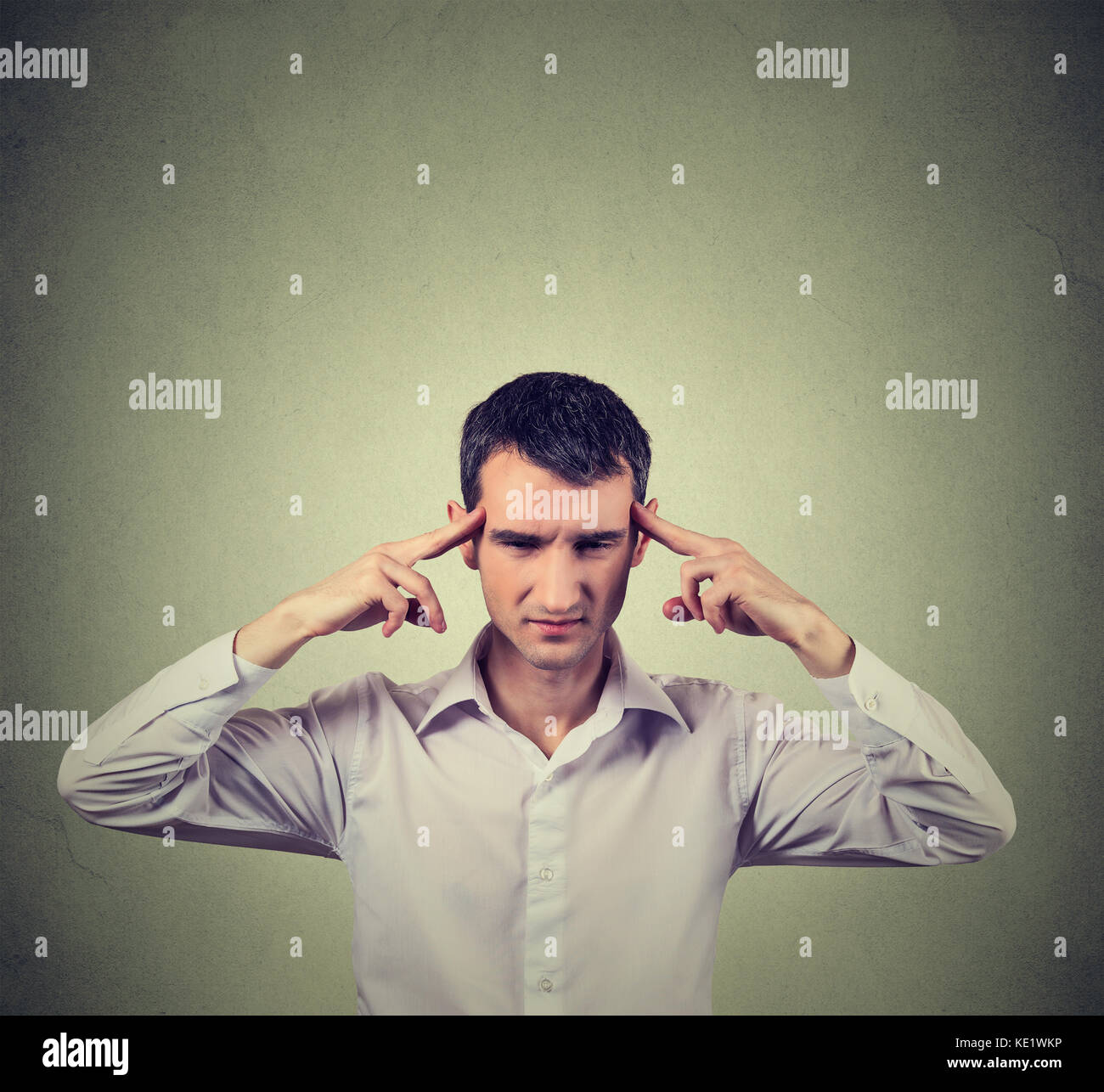 man thinking very intensely concentrating isolated on gray wall background - Stock Image