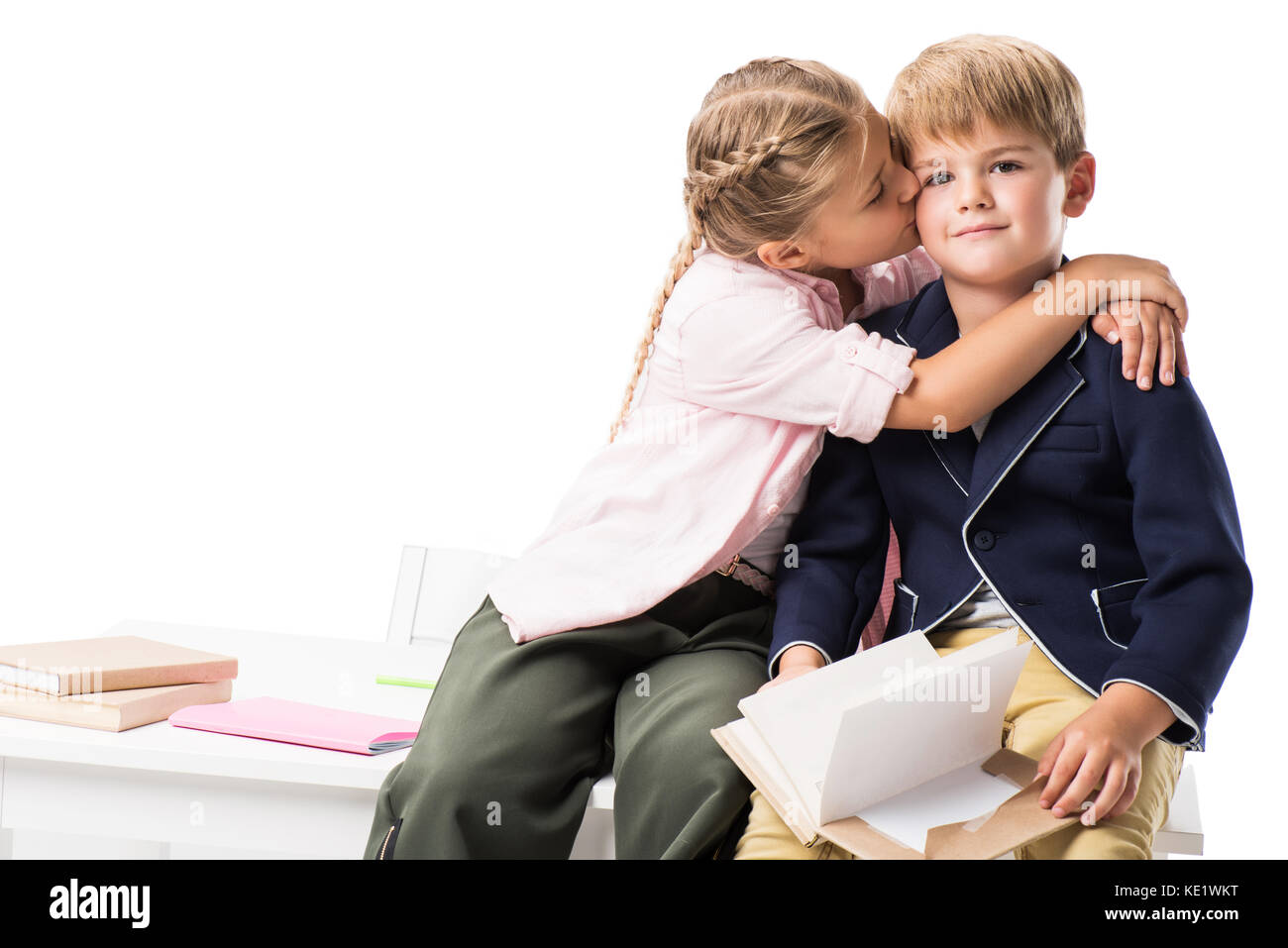 cute little girl kissing boy holding book and looking at camera isolated on white Stock Photo