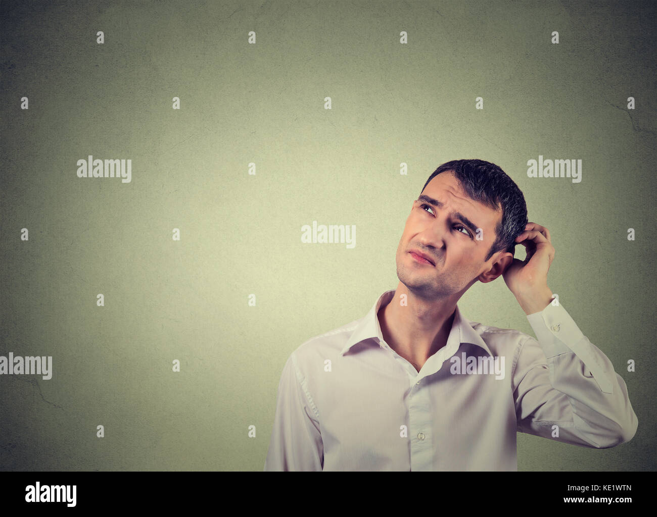 Closeup portrait man scratching head, thinking deeply about something, looking up, isolated on grey wall background. - Stock Image