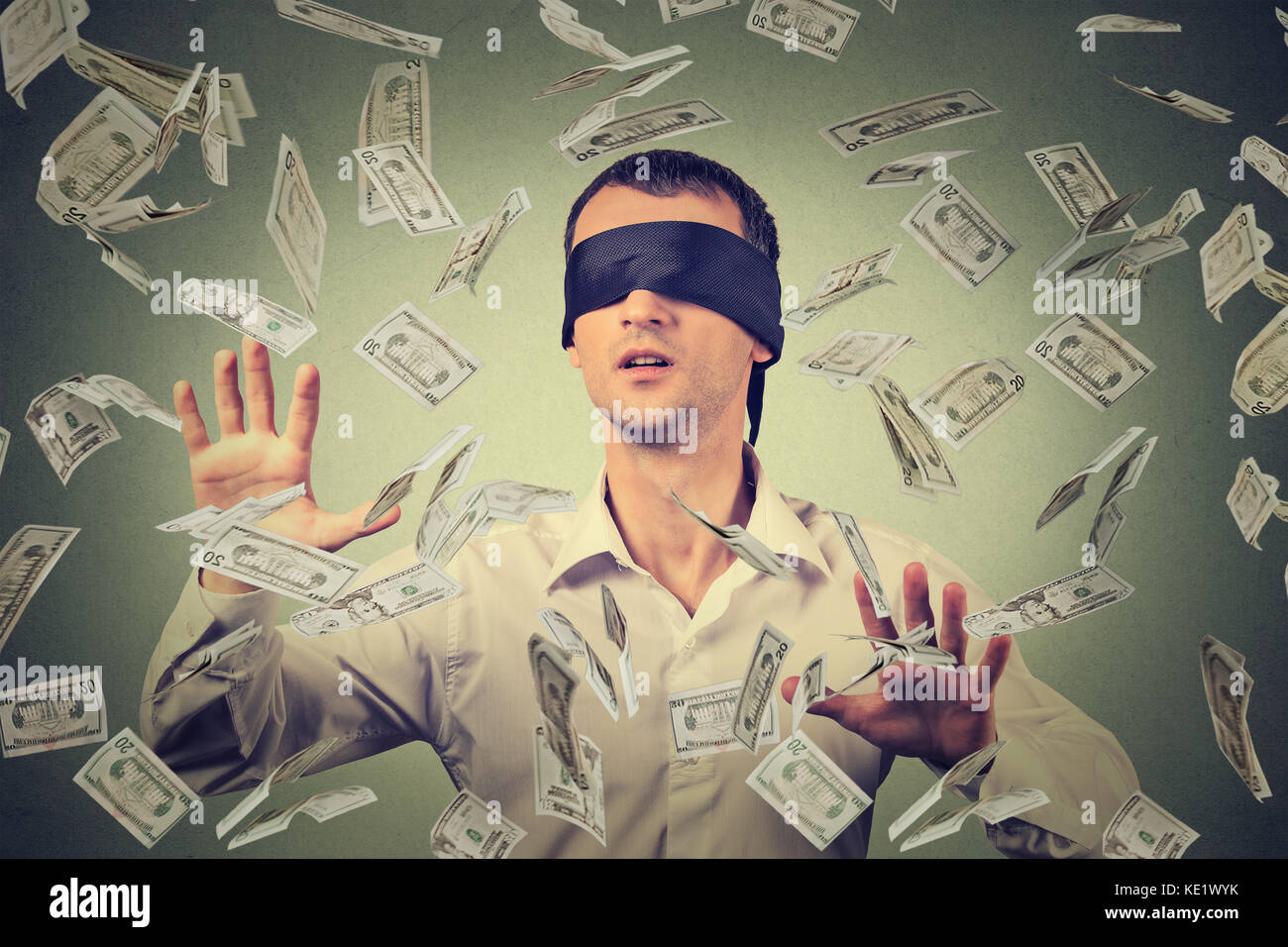 Blindfolded young businessman trying to catch dollar bills banknotes flying in the air isolated on gray wall background. - Stock Image