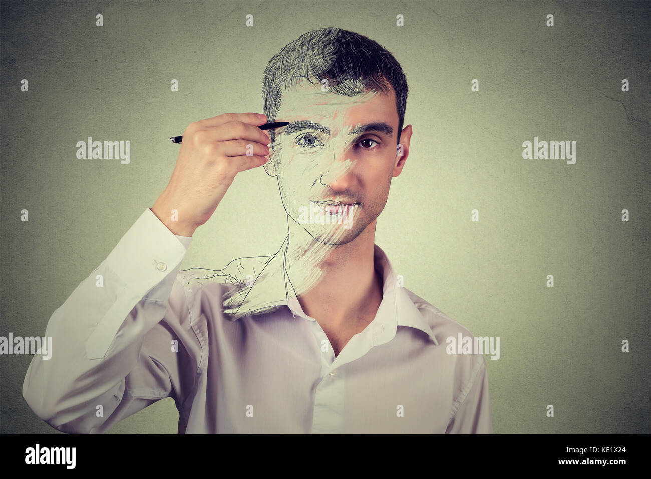 Young man drawing self portrait face, hiding true emotion isolated on grey wall background. Private life, identity - Stock Image