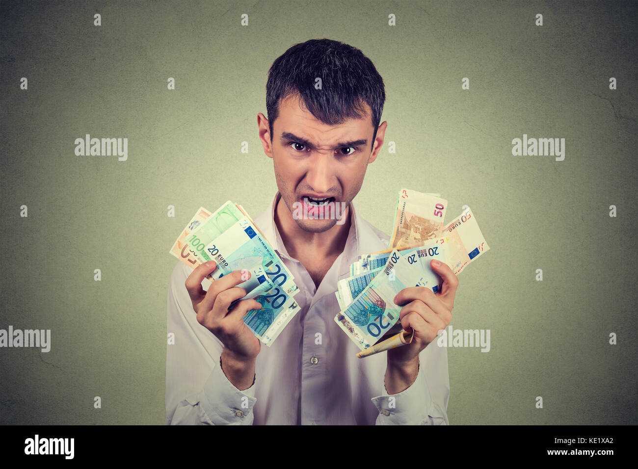 Greedy man with euro banknotes bills isolated on gray wall background - Stock Image