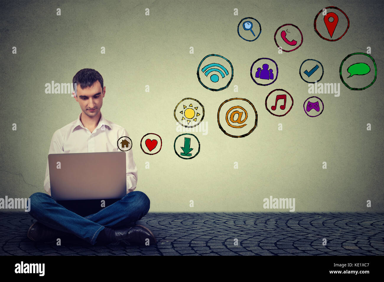 Young man working using laptop sitting on a floor social media application icons flying up. Modern communication - Stock Image