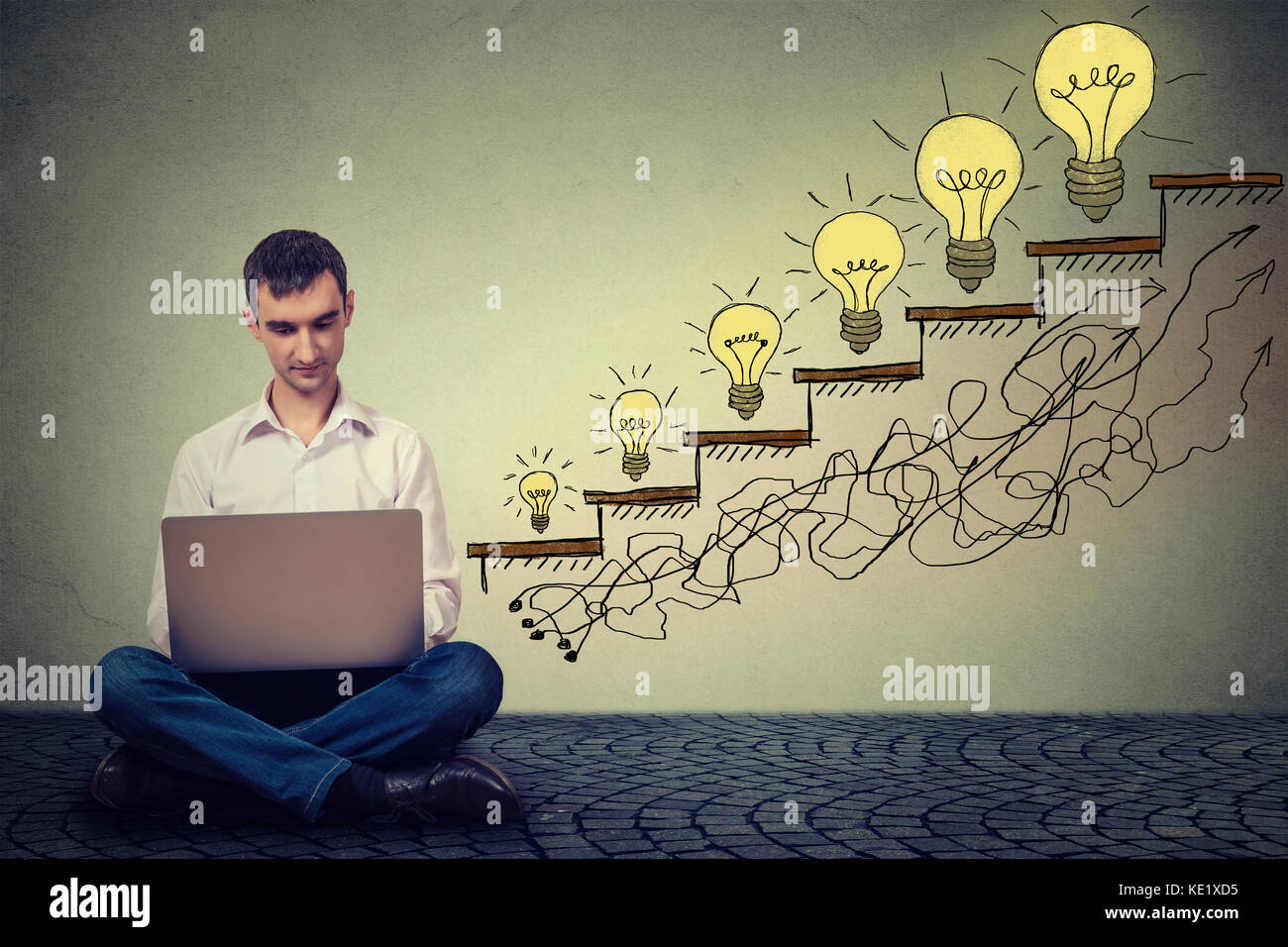 Happy young man entrepreneur working on computer sitting on a floor in his office successful in increasing internet - Stock Image
