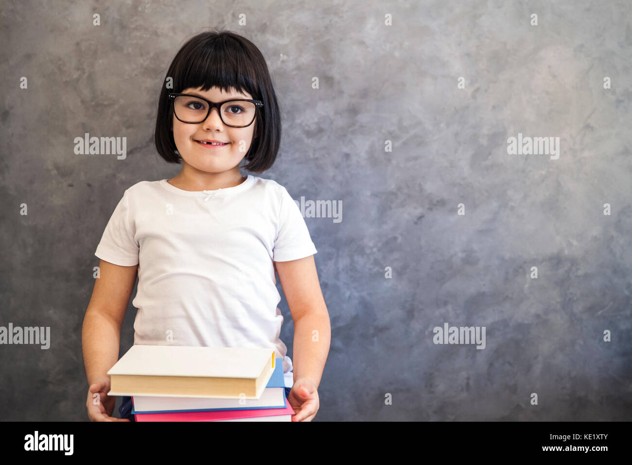 247fc37229c3 Portrait of smiling black hair little girl with glasses holding books by the  wall - Stock