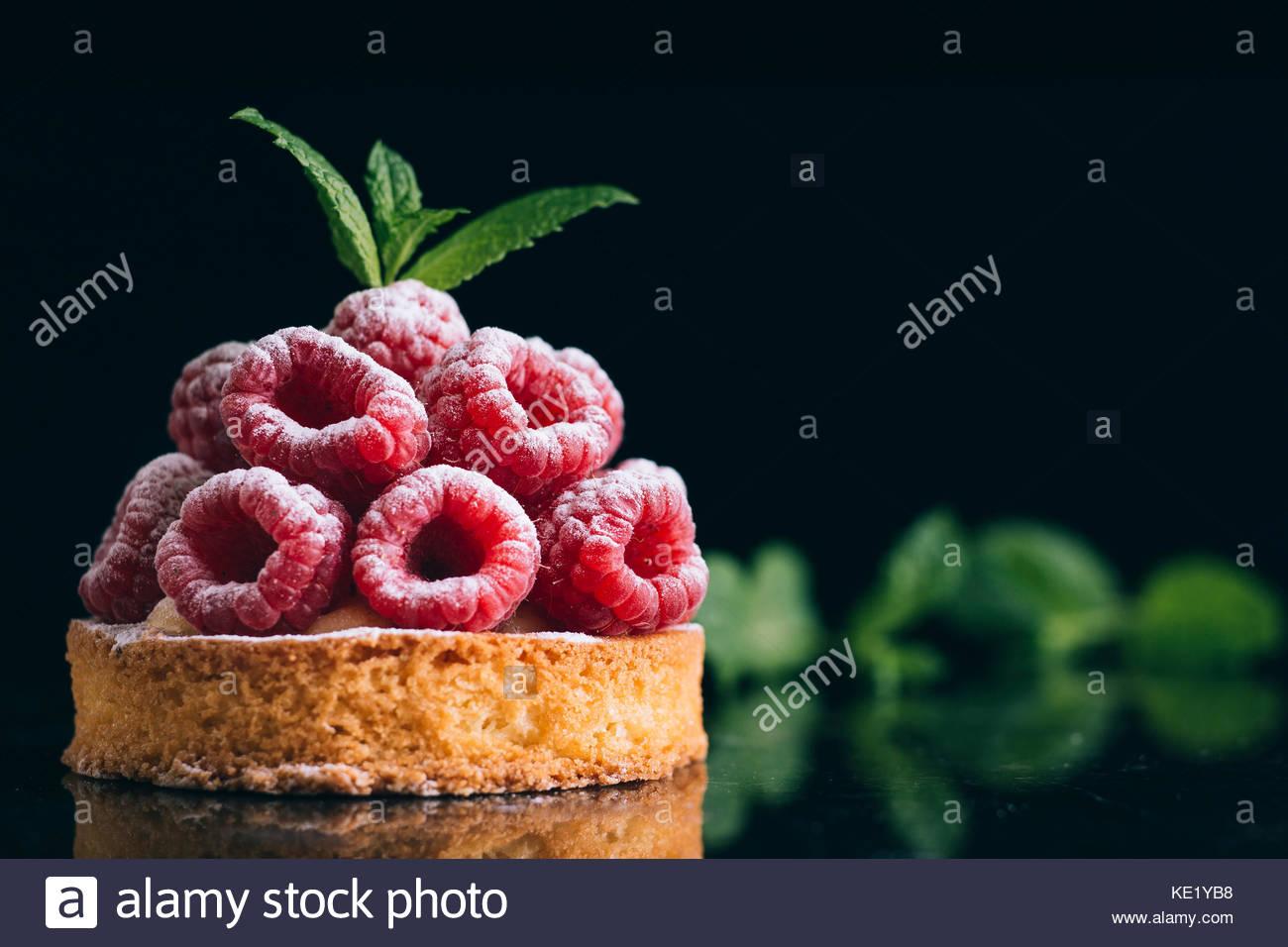 Raspberry tart dessert on dark background. Traditional french sweet pastry. Delicious, appetizing, homemade cake - Stock Image