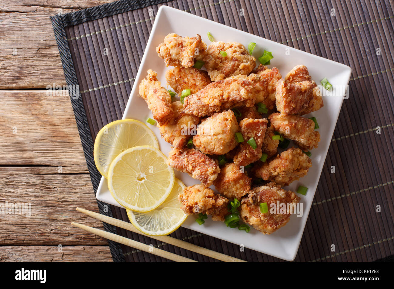Portion fried chicken karaage with lemon and onion close-up on a plate on the table. Horizontal top view from above - Stock Image