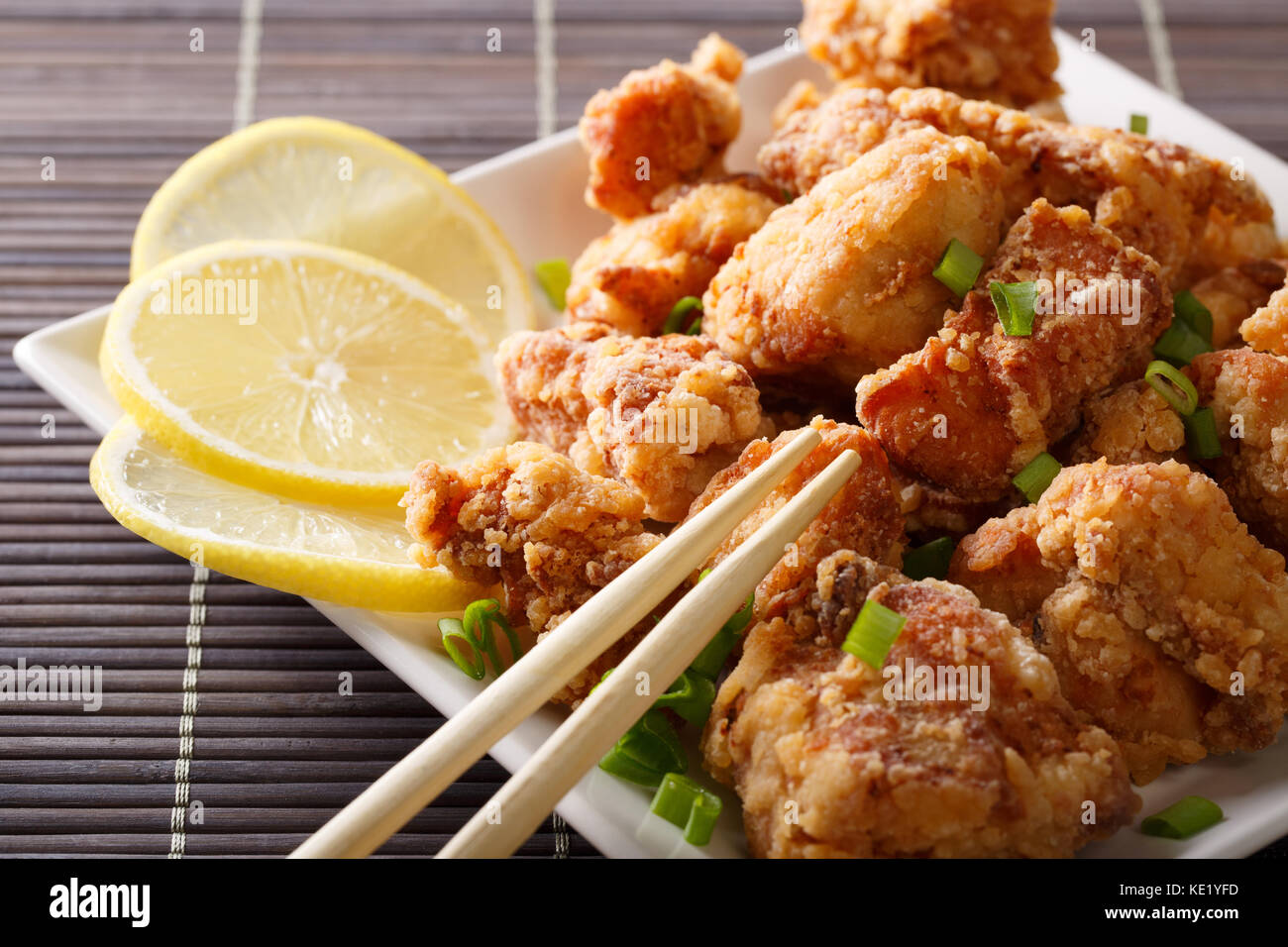Japanese dish: fried chicken karaage with a lemon close-up on a plate on the table. horizontal - Stock Image