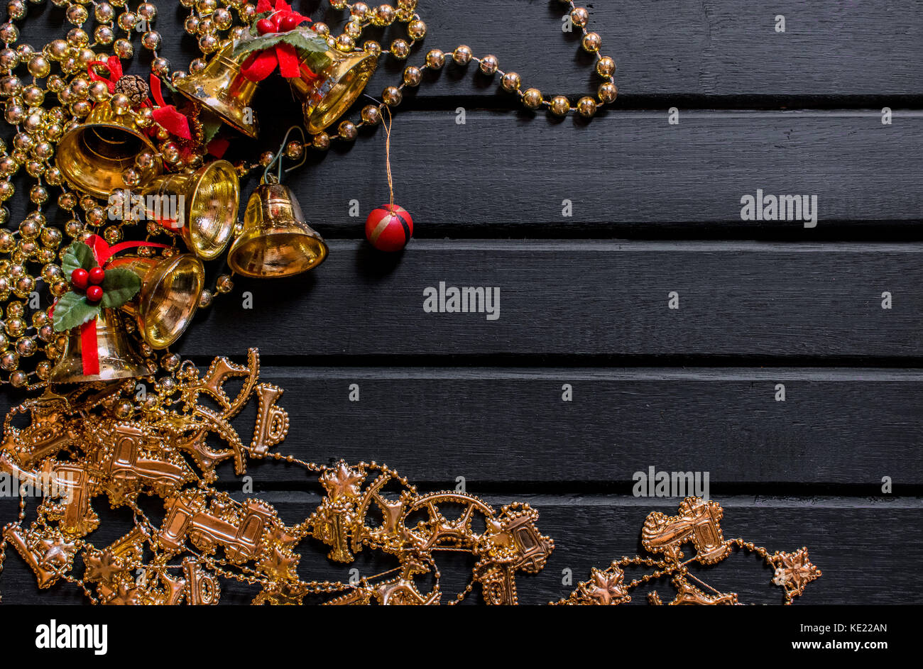 Christmas decoration background, on a black wooden backdrop, with bells, mistletoe, golden chains, balls and props - Stock Image