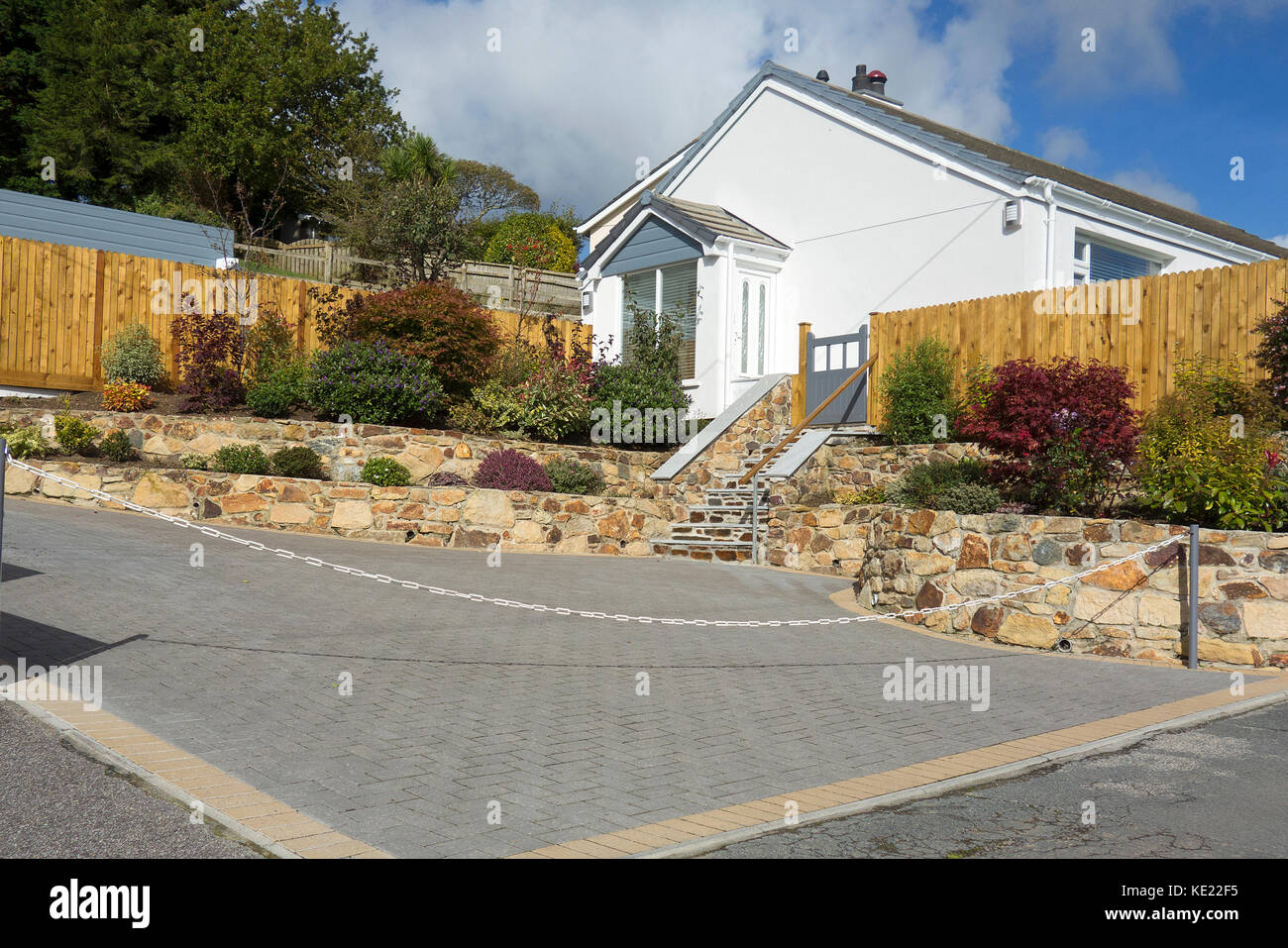 a garden paved with concrete blocks to make a driveway. - Stock Image