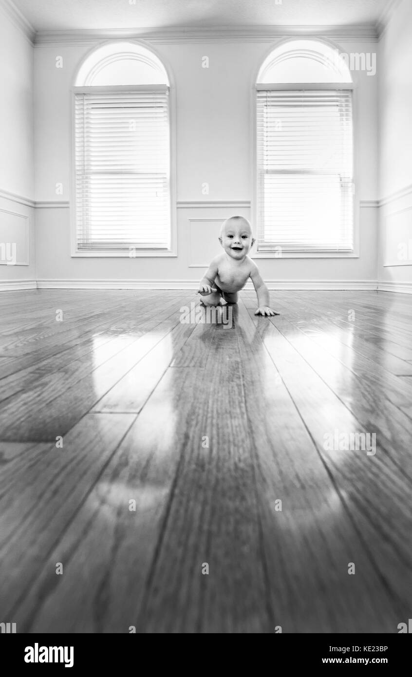 infant boy in an empty room - Stock Image