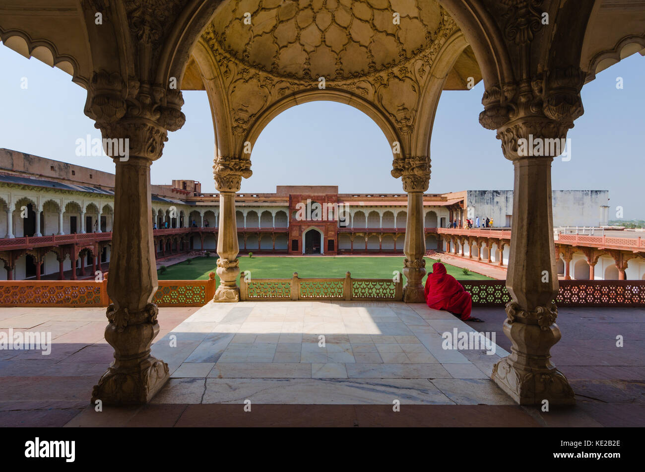 AGRA, INDIA - 4 MAY 2015: A woman drape din a red saree is sitting under the loggia facing the Jahangiri Mahal courtyard - Stock Image